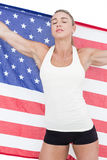 Female athlete holding American flag with closed eyes. On white background Royalty Free Stock Images