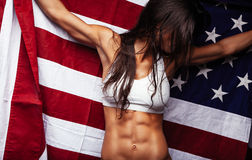 Female athlete holding American Flag. Looking away. Fit young woman wearing sports bar with United States of American flag Stock Photo
