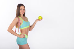 Female athlete holding an apple and measuring tape royalty free stock images