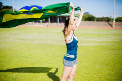 Female athlete holding an Brazilian flag. In the air Stock Photo