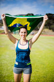 Female athlete holding an Brazilian flag. In the air Royalty Free Stock Image