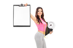 Female athlete holding clipboard and weight scale Royalty Free Stock Photos