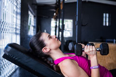 Female athlete holding dumbbell while lying on bench press Stock Image