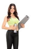 Female athlete holding an exercise mat Stock Image