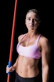 Female athlete holding a javelin. On black background Royalty Free Stock Photos