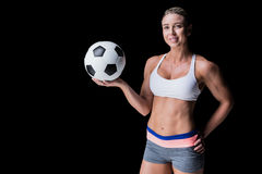 Female athlete holding a soccer ball. On black background royalty free stock images