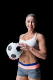 Female athlete holding a soccer ball. On black background stock photos
