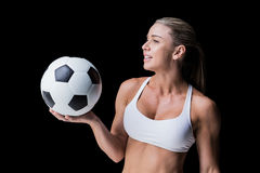 Female athlete holding a soccer ball. On black background stock images