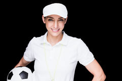 Female athlete holding a soccer ball. On black background royalty free stock photo