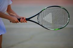 Female athlete holding tennis racket. Woman holding tennis racket on clay court. Close-up view of female hand and racquet Stock Photos