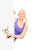 Female athlete holding a trophy behind a panel Stock Images