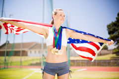 Female athlete holding up american flag with gold medal. In stadium Royalty Free Stock Photos