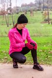Female athlete hurting from a knee injury on a cold winter day on the training track of an urban park. royalty free stock images