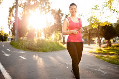 Female athlete jogging around the park at sunset Royalty Free Stock Photography