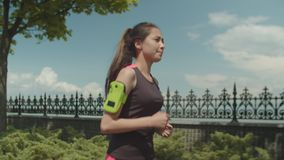 Female athlete jogging in city park during workout stock footage
