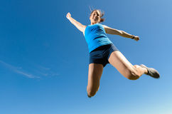 Female athlete Jumping. Happy woman jumping and celebrating success Royalty Free Stock Image