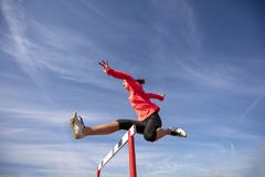Female athlete jumping above the hurdle during the race.  Royalty Free Stock Image