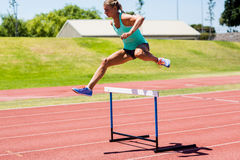 Female athlete jumping above the hurdle Stock Photography