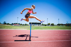 Female athlete jumping above the hurdle Stock Photo
