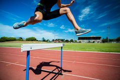 Female athlete jumping above the hurdle stock image