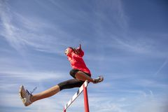 Female athlete jumping above the hurdle during the race.  Stock Photo