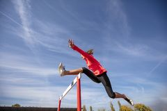 Female athlete jumping above the hurdle during the race.  Stock Image