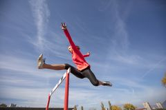 Female athlete jumping above the hurdle during the race.  Royalty Free Stock Photo