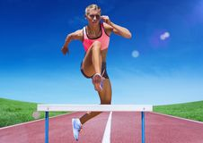 Female athlete jumping over hurdle on race track Stock Photos