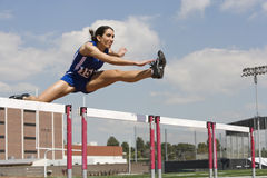 Female Athlete Jumping Over A Hurdles. Determined female athlete jumping over a hurdles Royalty Free Stock Photography