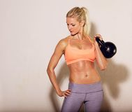 Female Athlete with a Kettlebell. Female athlete lifting a kettlebell Royalty Free Stock Images