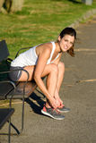 Female athlete lacing sport shoes before running in park Royalty Free Stock Images