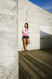 Female athlete leaning against wall with arms crossed Stock Photos