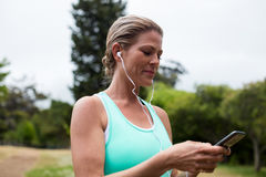 Female athlete listening to music on mobile phone Stock Images