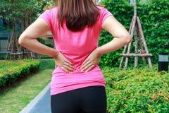 Female athlete lower back painful injury. Sporty woman backache Stock Photo