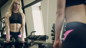 Female athlete makes deadlift exercise with dumbbells in gym. stock footage