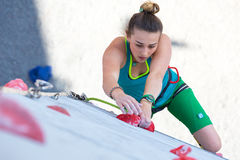 Female athlete makes hard move on climbing wall Royalty Free Stock Images
