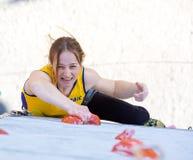 Female athlete makes hard move on climbing wall Royalty Free Stock Image