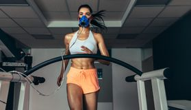 Runner testing her performance in sports science lab. Female athlete with mask running on treadmill to analyze her fitness performance. Runner testing her Royalty Free Stock Images
