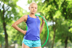 Female athlete on a mat holding a hula hoop in park Royalty Free Stock Photos