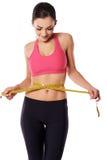 Female athlete measuring her waist Royalty Free Stock Image