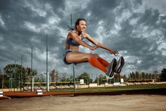Female athlete performing a long jump during a competition. At stadium. The jump, athlete, action, motion, sport, success, championship concept royalty free stock photo