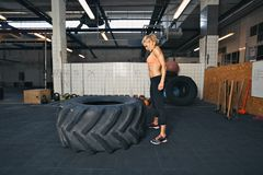 Female athlete performing tire flipping crossfit exercise Stock Photography