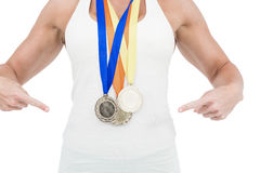 Female athlete pointing her medals Royalty Free Stock Photography