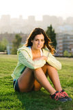 Female athlete portrait in city park. Cheerful female athlete portrait in city park on sunset or morning. Beautiful sporty woman taking a workout break Stock Photo