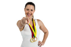 Female athlete posing with gold medals around his neck Stock Photography