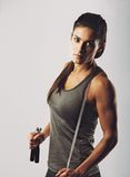 Female athlete posing with jumping rope. Confident young mixed raced female athlete posing with jumping rope looking at camera. Muscular woman with skipping rope Stock Image