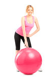 A female athlete posing next to a pilates ball Royalty Free Stock Photo