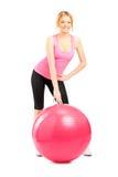 A female athlete posing next to a pilates ball Royalty Free Stock Photo