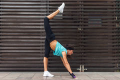 Female athlete practicing yoga exercise by stretching her legs outdoors. Sporty young woman doing standing split pose on Stock Photos