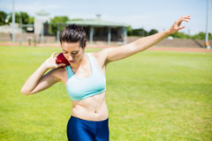 Female athlete preparing to throw shot put ball Stock Photo
